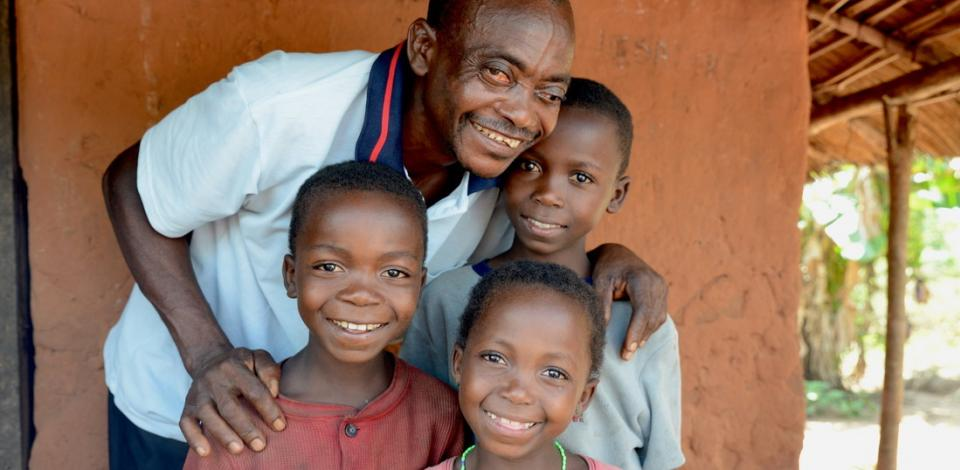 Vincent together with three of his children: Joseph (10, dark-red shirt), Mado (12, bright shirt) and Elysee (6, in front).Vincent (50) lost the eyesight of his left eye due to onchcerciasis - but Mectizan® saved the vision of his right eye.