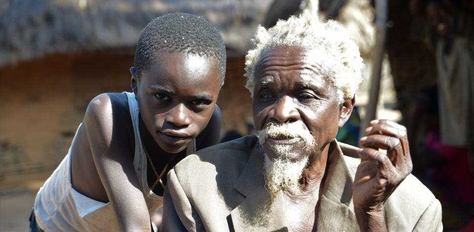 © CBM/Tobias Pflanz. Albert (74) is blind due to onchocerciasis. Here with his grandson Marceil (7).